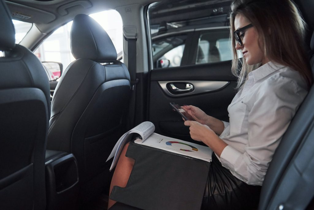 Documents in the notepad. Smart businesswoman sits at backseat of the luxury car with black interior