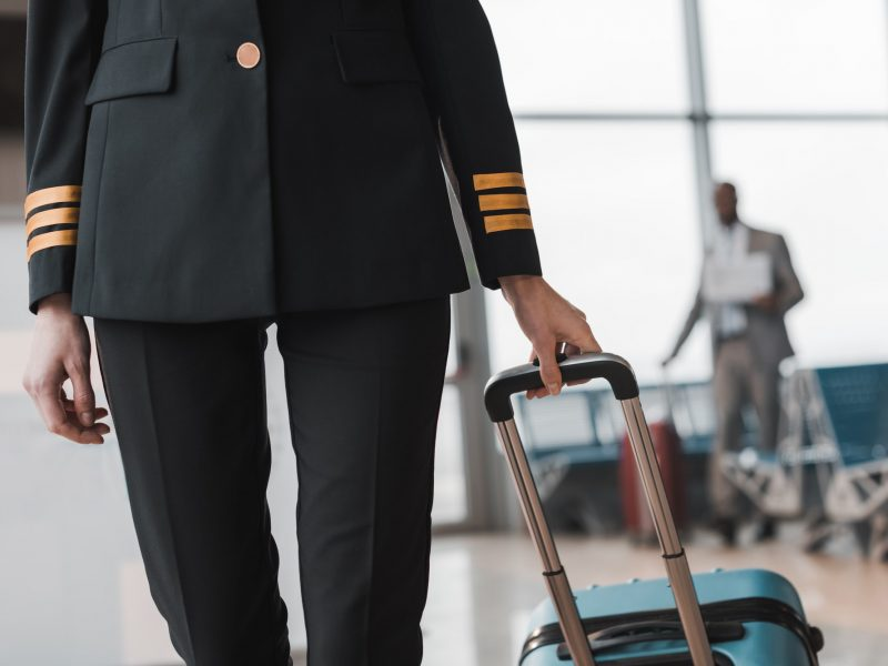 cropped shot of female pilot with suitcase walking by airport lobby